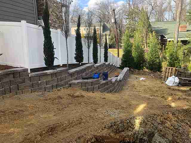 Retaining wall with shrubs planted in front of white fence